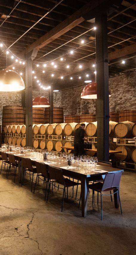 A table is set for a wine tasting in the Larkmead Building, while wine barrels age in the background