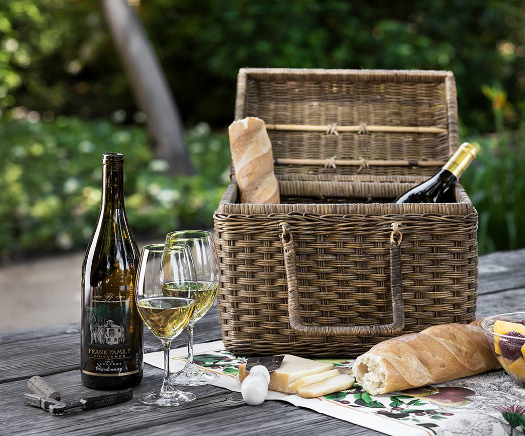 A picnic basket sits on a table with food and wine beside it