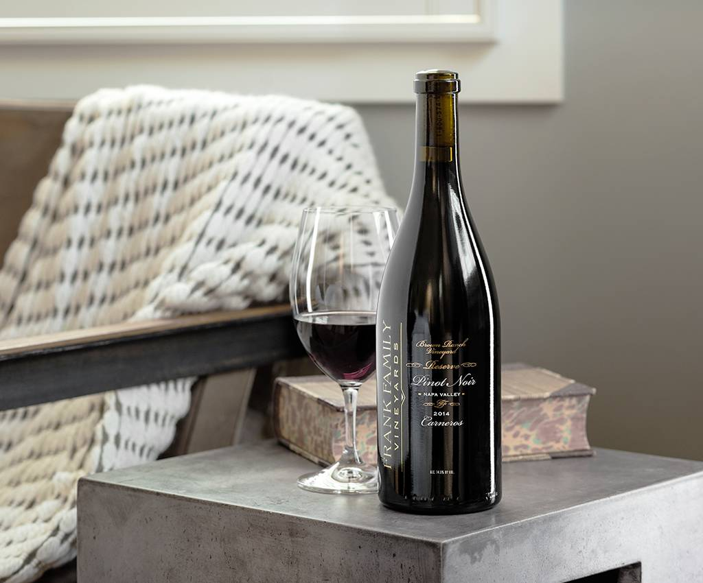 A glass of poured wine rests next to a bottle of Frank Family Pinot Noir
