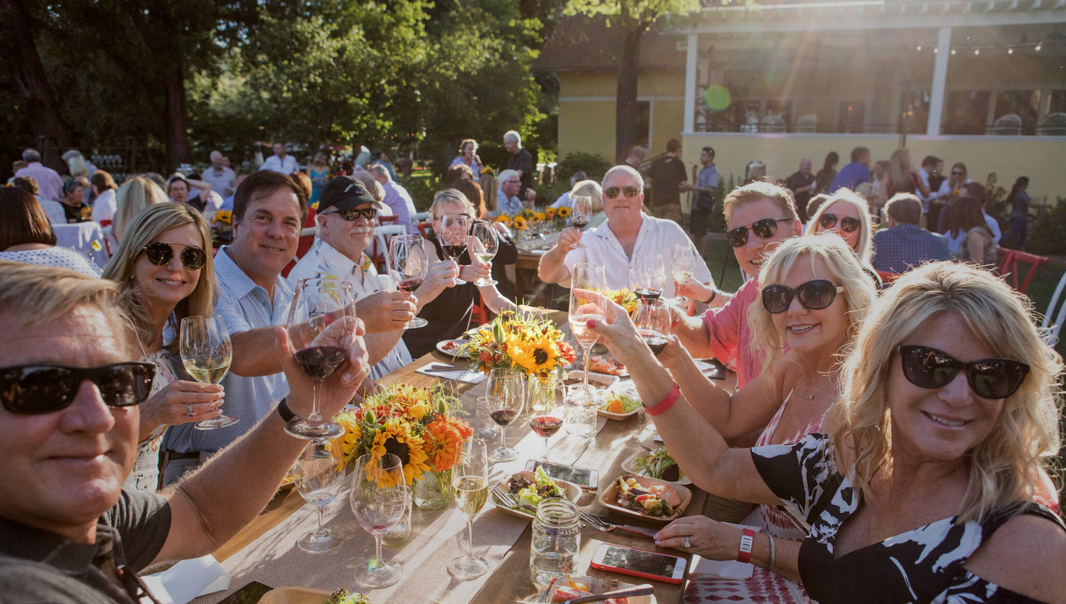 A crowd toasts at an outdoor event during sunset