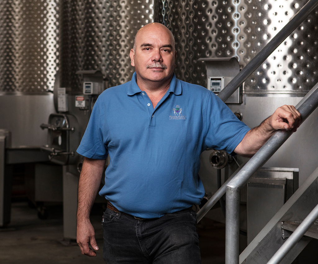 Armando pauses for a picture along side a wine fermenter